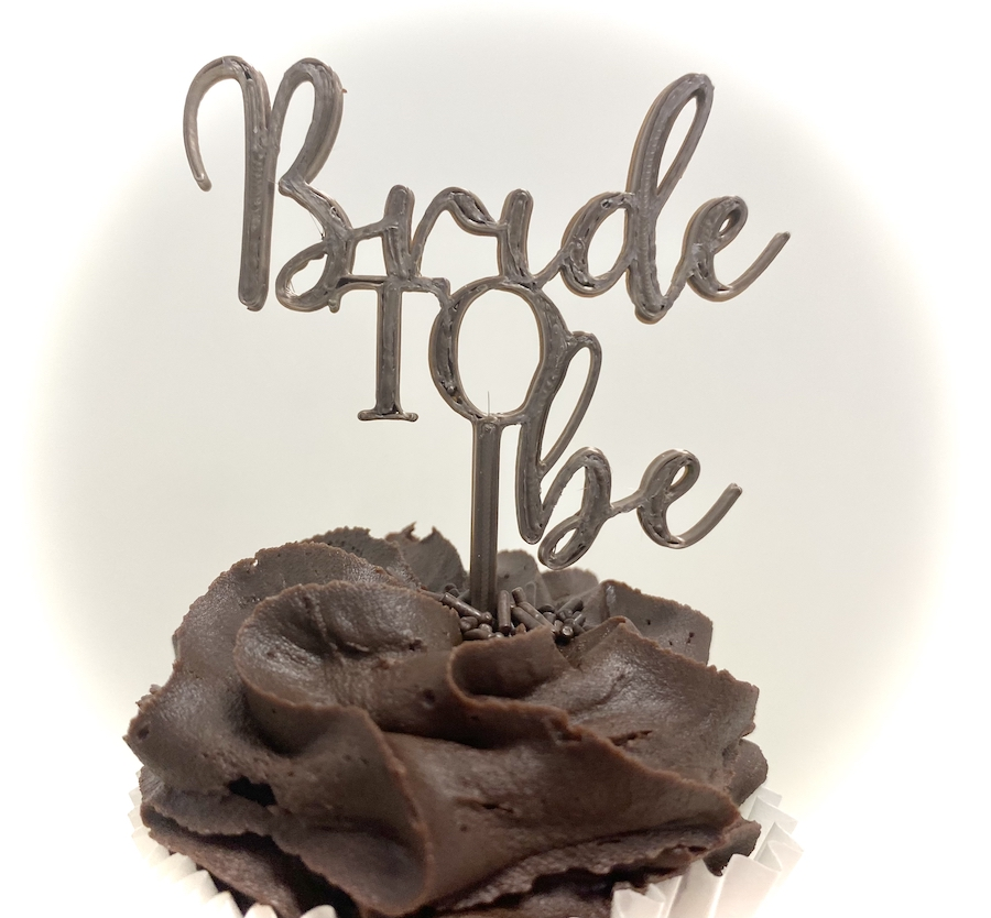 """Plastic cake topper reads """"Bride to Be"""""""